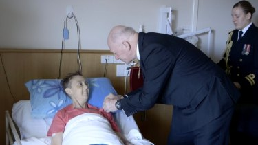 Sir Peter Cosgrove presents Connie with her medal during a special bedside ceremony.
