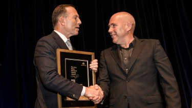 Prime Minister Tony Abbott presents Richard Flanagan with the 2014 award for best fiction.