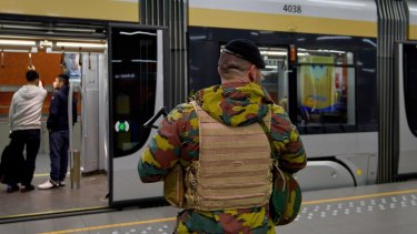 An armed soldier stands guard on the platform of De Brouckere Metro Station in Brussels, Belgium.