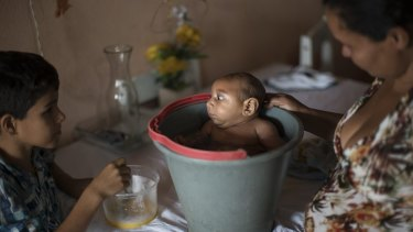 Elison, 10, watches as his mother Solange Ferreira bathes Jose Wesley in a bucket at their house.