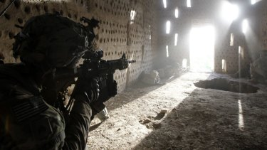 A US soldier points his rifle at a doorway after coming under fire by the Taliban in southern Kandahar province in 2012.