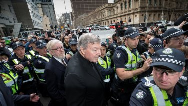 Cardinal George Pell, with his lawyer Robert Richter QC, leave court amid chaotic scenes.