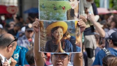 Supporters of Thailand's former Prime Minister Yingluck Shinawatra display her images outside the Supreme Court after Yingluck failed to show up to hear a verdict in Bangkok, Thailand.