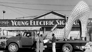 The use of neon seems almost limitless as a giant shoe is loaded for transport.
