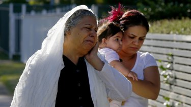 Relatives of the shooting victim comfort each other in Matthew Street, Heckenberg.