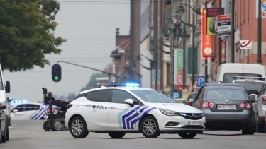A police vehicle blocks a road in front of an explosives robot.