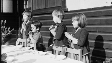 Young children say grace at a dining table at Dalwood Children's Home in 1932.
