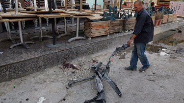 A man clears debris from the aftermath of a massive bombing in central Baghdad.