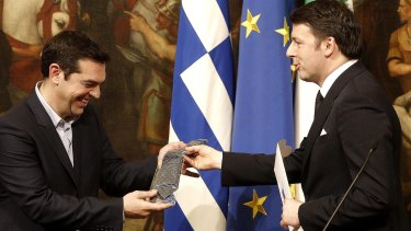A lesson in Italian style: Greek Prime Minister Alexis Tsipras is presented with a tie by Italian Premier Matteo Renzi at the end of a joint press conference at Rome's Palazzo Chigi government office.