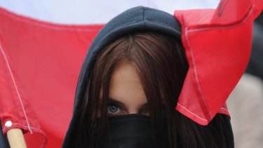 A masked protester holds a Polish flag during a right-wing nationalist march in Warsaw, demonstrating against EU-proposed quotas to spread the human tide of refugees around Europe.