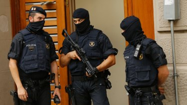 Police officers stand outside a building during a search in Ripoll, north of Barcelona.