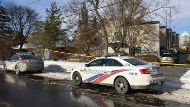 Police cars parked outside the home of billionaire Barry Sherman.