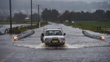 Local farmer crosses the flooded Illawarra Highway at Albion Park after heavy falls across the region.