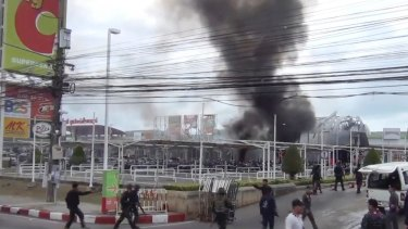 Smoke rises from an exploded vehicle outside a popular shopping centre in Pattani province, southern Thailand.