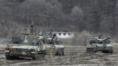 South Korean army soldiers stand on their K-55 self-propelled howitzers during exercises near the North Korean border.