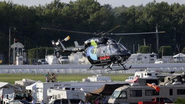 A helicopter lifts off at Pocono Raceway carrying race car driver Justin Wilson.