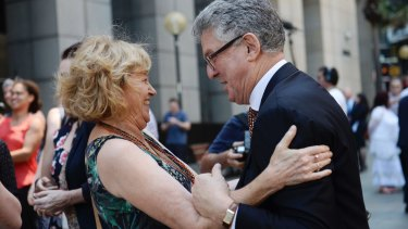 Joan Isaacs, one of the first to give evidence against the Catholic Church, hugs David Marr outside the Royal Commission.