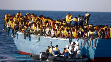 Italian officers rescue a woman from a crowded wooden boat carrying more than seven hundred migrants, during a rescue operation in the Mediterranean, off Libya last month.