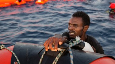 A refugee from Eritrea grabs a dinghy after jumping into the Mediterranean from a crowded wooden boat.
