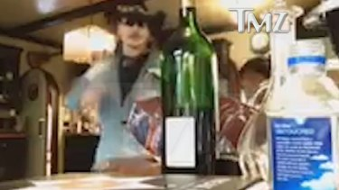 Johnny Depp reaches for a bottle of wine in the video.