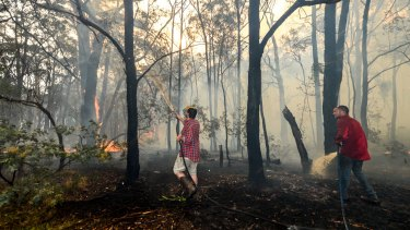 Adam Watkins and partner Prue Mathiesen fight the fire to save their rented home in Lancefield.
