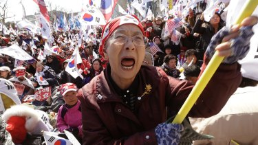 A supporter of South Korean President Park Geun-hye cries during a rally opposing her impeachment near the Constitutional Court in Seoul, South Korea, on Friday