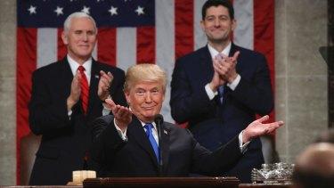 President Donald Trump gestures as Vice President Mike Pence and House Speaker Paul Ryan applaud.