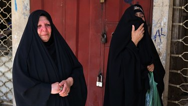 Women grieve at the site of a deadly bomb attack, in Baghdad, Iraq.