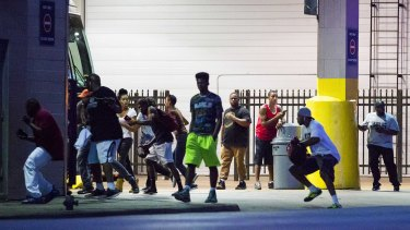 Bystanders run for cover after shots were fired at a Black Live Matter rally in downtown Dallas.