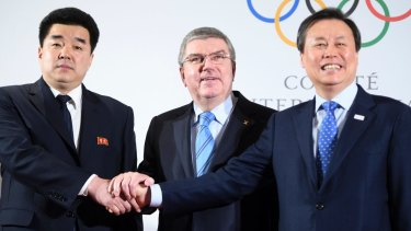 Show of unity: IOC president shakes hands with North and South Korean ministers.