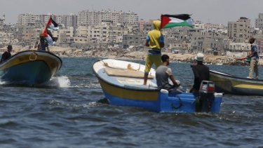 Palestinians riding boats hold Palestinian flags during a protest against the Israeli blocking of a boat of foreign activists from reaching Gaza, at the Seaport of Gaza City on Monday.