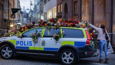 A woman drops flowers onto a police car near the department store Ahlens following a suspected terror attack in central Stockholm.