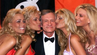 Playboy founder and editor in chief Hugh Hefner receives kisses from Playboy playmates during the 52nd Cannes Film Festival in Cannes, France in 1999.