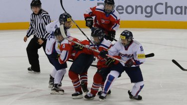 South, wearing white, and North Korean players, in red, compete during a women's ice hockey world championship game last month.