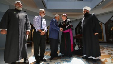 Catholic Archbishop of Sydney Most Rev, Anthony Fisher and Grand Mufti Dr Ibrahim Abu Mohammad of the Australian National Imams Council shake hands.