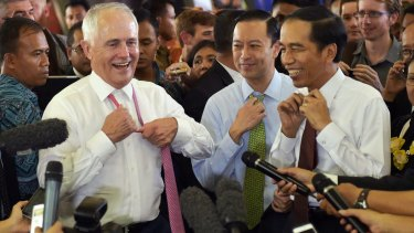 Australian Prime Minister Malcolm Turnbull and Indonesian President Joko Widodo move to take off their ties during a visit to a Jakarta market. Standing between them in the blue shirt is Thomas Lembong.
