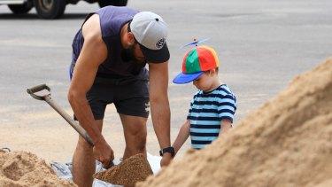 Orlando Bryson helps his dad, Dylan, with the sandbagging.