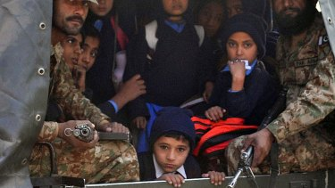 Pakistani soldiers transport rescued school children from the site of an attack by Taliban.