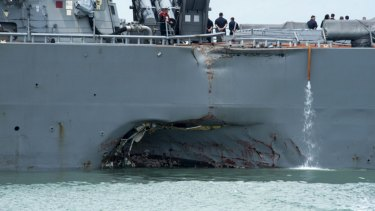 Damage to the portside is visible as the Guided-missile destroyer USS John S. McCain steers towards Changi naval base in Singapore following a collision with the merchant vessel Alnic MC.