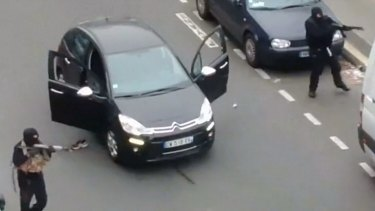 Gunmen flee the offices of French satirical newspaper <i>Charlie Hebdo</i>.