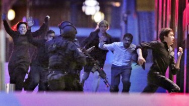 Hostages flee from the Lindt cafe.
