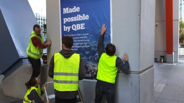 Eight activists pasted images of damaged coral reef and major fuel projects at QBE's headquarters in Sydney.