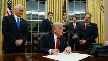 Vice President Mike Pence watches at left as President Donald Trump prepares to sign his first executive order in the Oval Office of the White House in Washington.