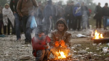 Two boys warm themselves by a fire while other migrants and refugees walk towards the transit camp for refugees near the southern Macedonian town of Gevgelija after crossing the border from Greece.