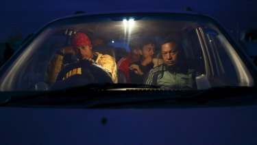 People sit inside their car on open ground to keep safe after an earthquake in Kathmandu.