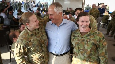 Prime Minister Malcolm Turnbull poses for photos with Lance-Corporal Blaire Harris (left) and Private Georgia Gilbertson (right) during breakfast at Camp Baird ahead of his visit to Iraq.