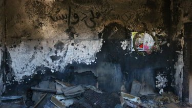 A child's burnt clothing and belongings can still be seen on the floor of the Dawabshe family home. Ali Dawabshe's name is written in Arabic on the wall.