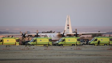 Ambulances line up as emergency workers unload bodies of victims from the crash.