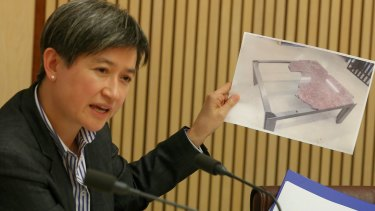 Senator Penny Wong holds up the photo of the damaged marble table during the Senate hearing on Monday.