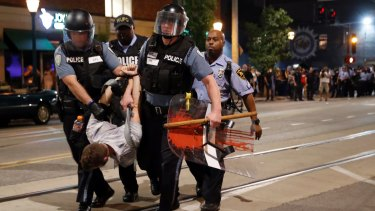 Police arrest a man as they try to clear a violent crowd in University City.